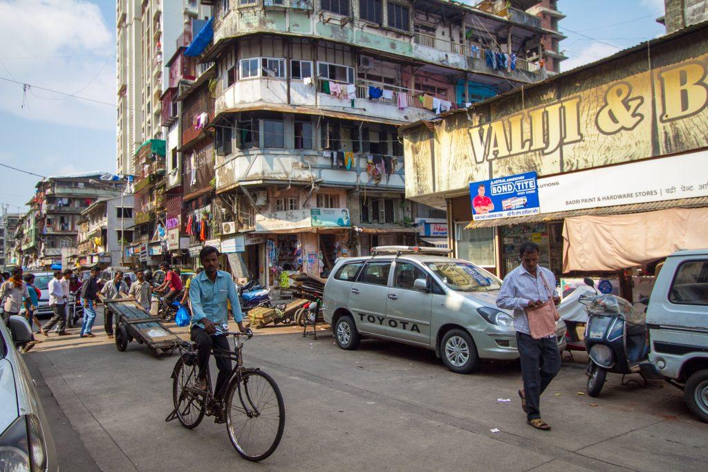 cyclist, street scene and apartment block in Mumbai India