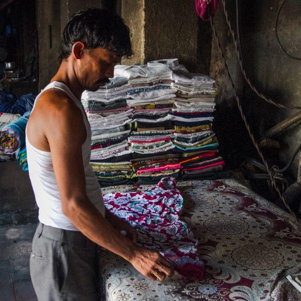 Man ironing in Dhobi Ghat laundry
